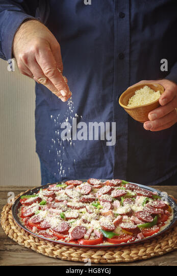 Man in a blue shirt sprinkle with cheese pizza from a ceramic sauser vertical - Stock Image