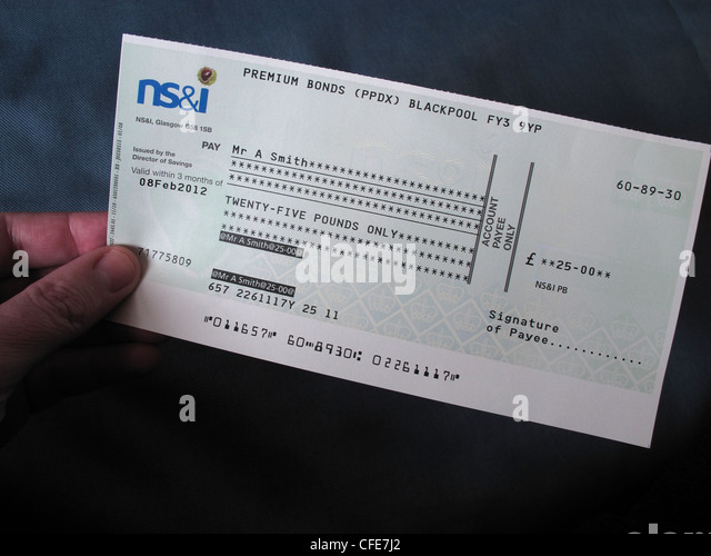 NS&I premium bond cheque held in a hand of the lucky winner - Stock Image