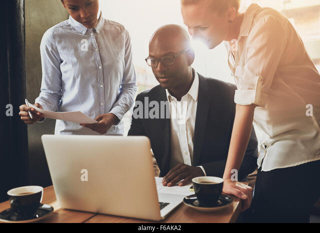 Ethnic business people, entrepreneurs working together using a laptop - Stock Image