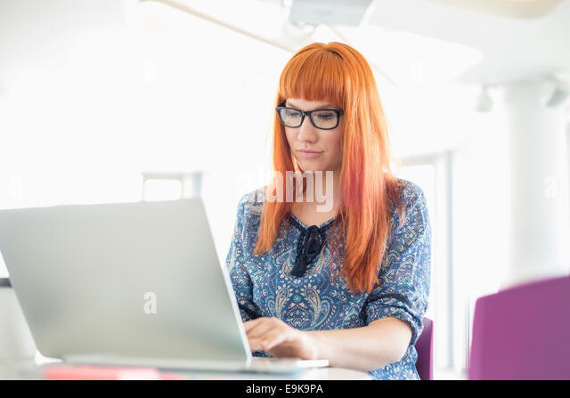 Businesswoman working on laptop in creative office - Stock Image
