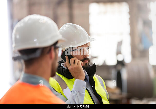 Steel workers talking on cell phone in factory - Stock Image