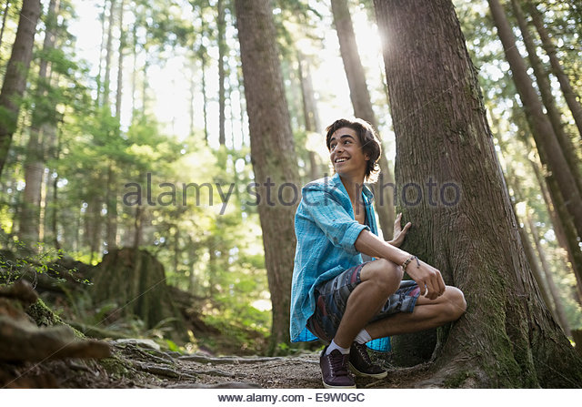 Teenage boy crouching by tree in woods - Stock Image