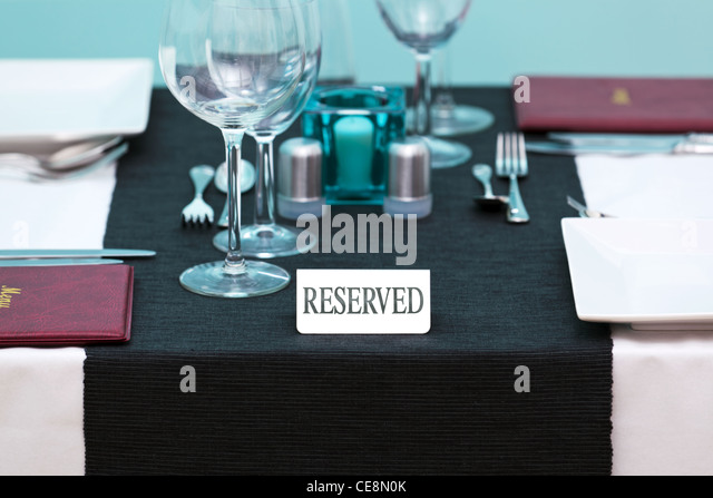 Photo of a Reserved sign on a restaurant table with menus on the side and place settings for two people. - Stock Image