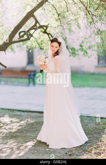 Side view of shy bride  looking down holding flower bouquet in garden, park - Stock Image