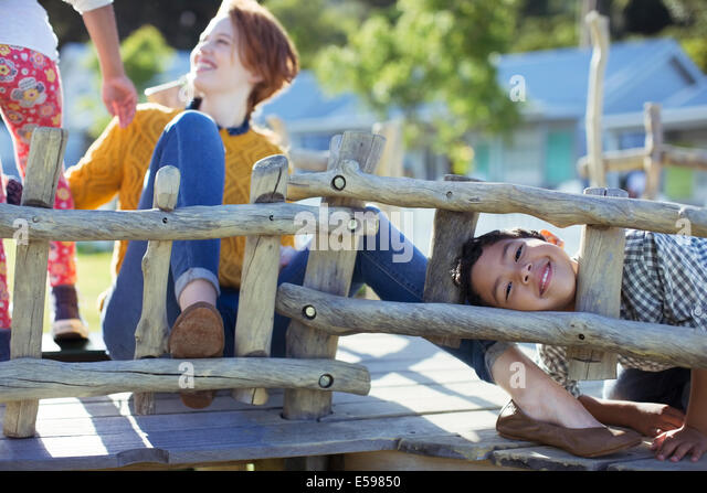 Teacher and students playing on play structure - Stock Image