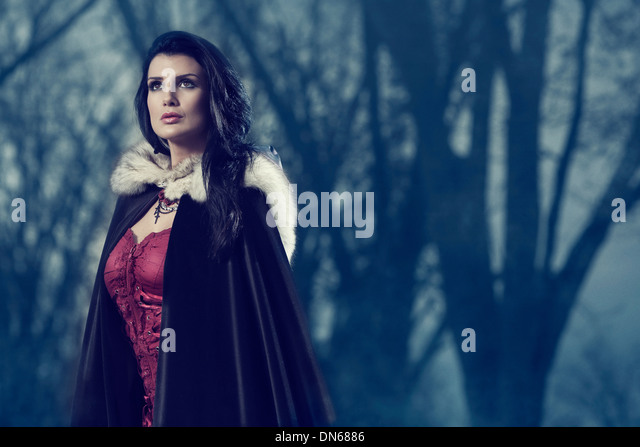 Woman outside among trees in the fog wearing a dark cape - Stock-Bilder