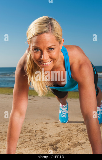 Portrait of woman doing press-ups on beach - Stock Image