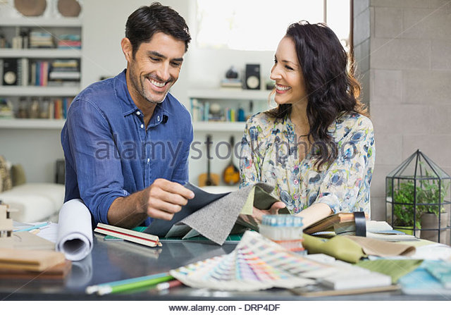 Design professionals with fabric swatches in home office - Stock Image