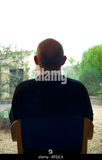 A man sitting viewing his garden through a large window - Stock Image