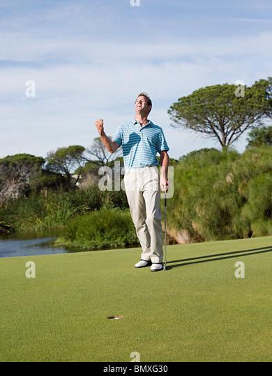Ecstatic man playing golf - Stock Image