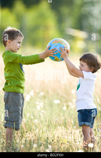 Kids playing with globe on meadow - Stock Image