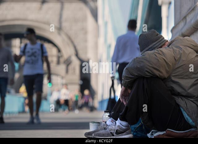 Homeless man begging on Tower Bridge in London, England, UK - Stock Image