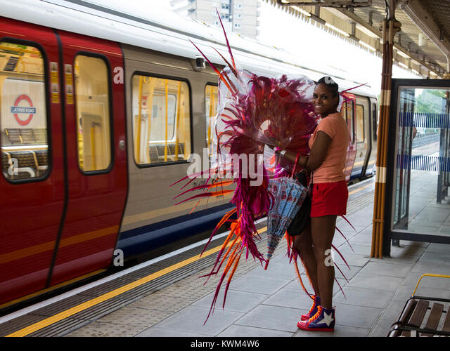 Young woman carrying a costume on her way to the Notting Hill Carnival on the London Underground - Stock Image