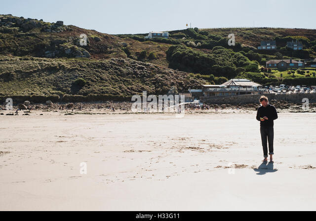 A lone man checking his phone on the beach at Sennen Cove, Cornwall - Stock Image