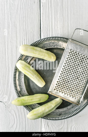 Peeled cucumbers in the metal plate with grater top view - Stock Image