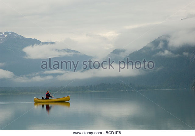 A woman and her dog paddle across a still Chilkoot Lake in Alaska. - Stock Image