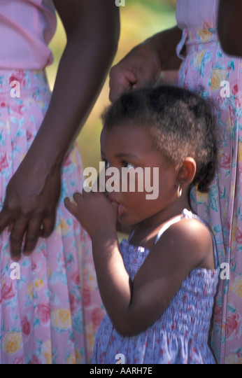 Honduras Garifuna young girl sucking her thumb - Stock Image