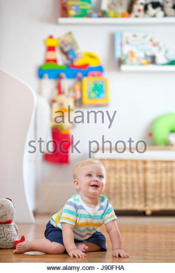 Baby Boy Playing On Floor In Nursery - Stock-Bilder
