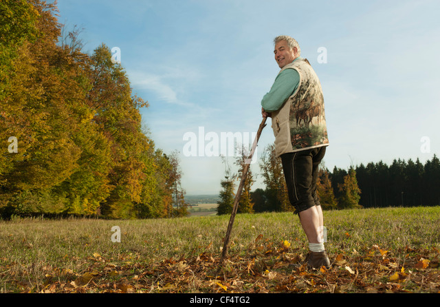 Germany, Bavaria, Mature man in traditional vest with cane, smiling, portrait - Stock Image