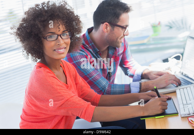 Graphic designer using a graphics tablet in her office - Stock Image