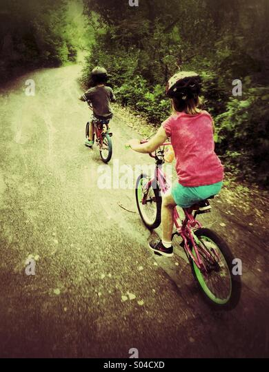 Two children ride their bicycles on a path through the woods. - Stock Image
