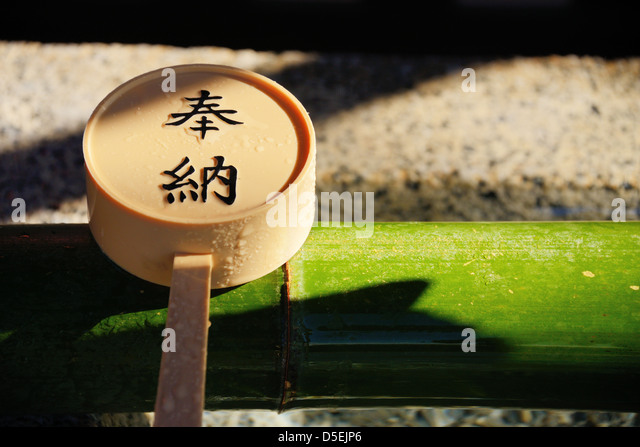 Scoop set atop a ritualistic tsukubai hand-washing basin with Japanese Kanji charachters reading 'dedication.' - Stock Image
