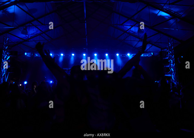 concert goers with arms in the air in front of stage lighting at a dance event in Belfast Northern Ireland - Stock Image