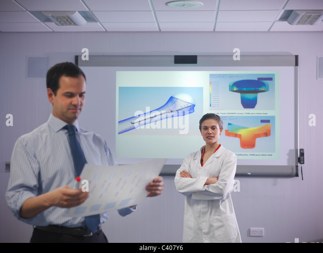 Scientists in front of product designs - Stock Image