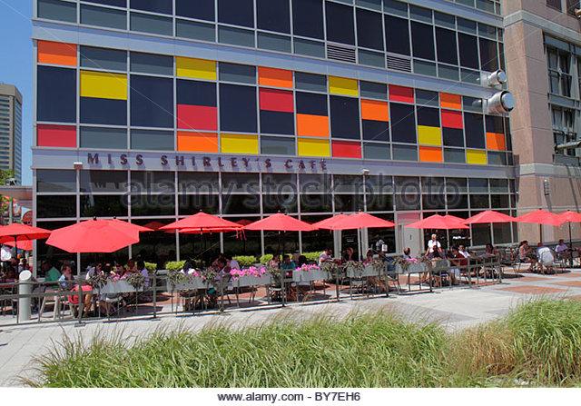 Maryland Baltimore East Pratt Street Miss Shirley's Cafe restaurant business sidewalk table umbrella man woman - Stock Image