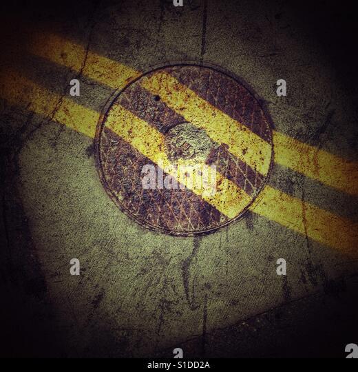 Manhole cover double yellow lines - Stock-Bilder