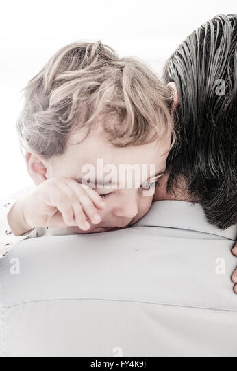 a small boy in father arms crying - Stock Image