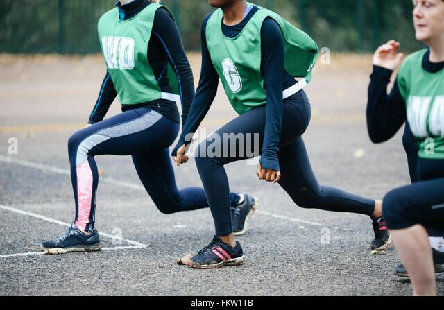 Cropped view of female netball players warming up on netball court - Stock Image
