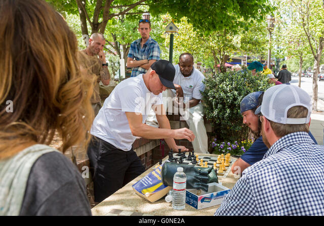 Asheville, North Carolina - Actor Woody Harrelson (black cap) plays chess in Pritchard Park. Many park regulars - Stock Image