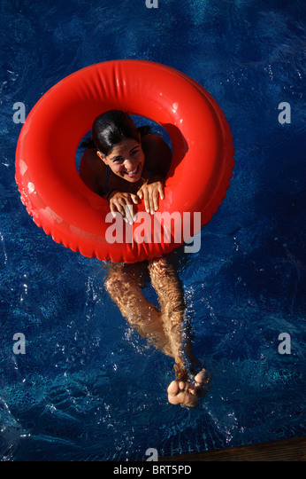 Cute caucasian young woman in a swimming pool with red lilo from above - Stock Image