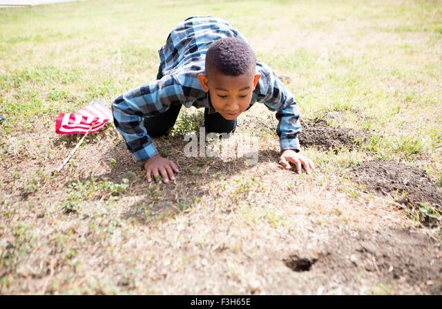 Boy crawling, peering into hole in ground - Stock Image