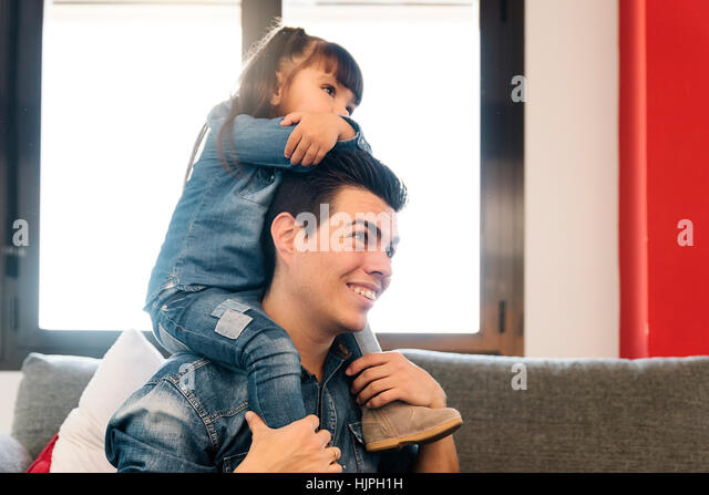 Proud father piggybacking his daughter at home. - Stock Image