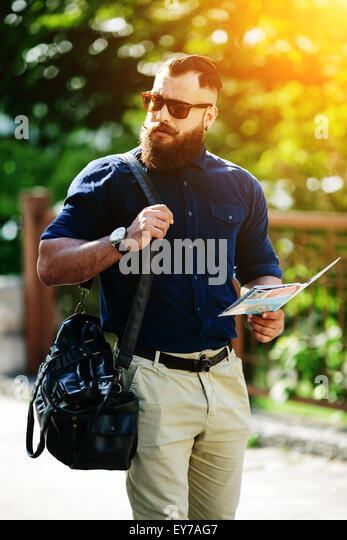 bearded man with a map in hand - Stock-Bilder