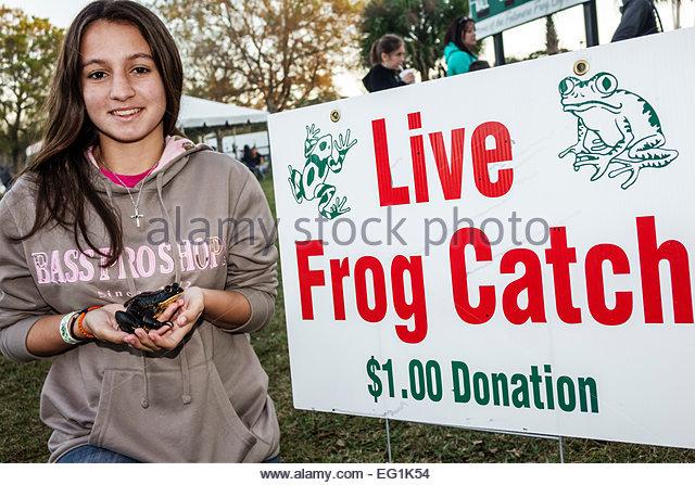 Florida Fellsmere Frog Leg Festival live frog catch game donation teen girl volunteer - Stock Image