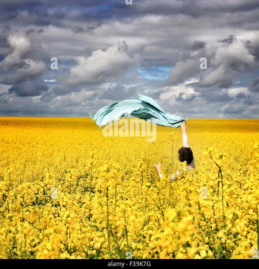 Woman standing in a rapeseed field waving a scarf in the air - Stock Image