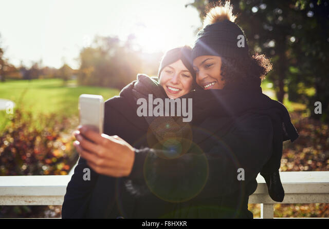 Two smiling young women taking selfie against of autumnal park - Stock Image