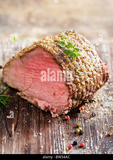 juicy roast beef covered in herbs - Stock Image