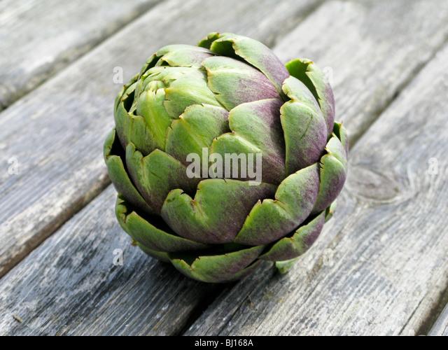 A globe artichoke on a wooden table - Stock Image