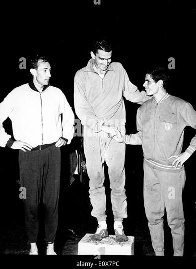 RON CLARKE, center, after winning a 5000m race at Charltey Stadium. - Stock Image