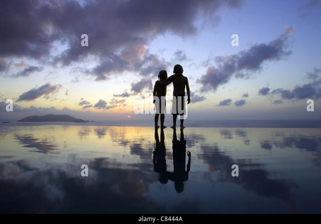 Children standing on beach at sunset - Stock-Bilder