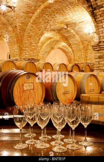 Wine aging in barrels in cellar with wine glasses. Castello di Amorosa. Napa Valley, California. Property released - Stock Image
