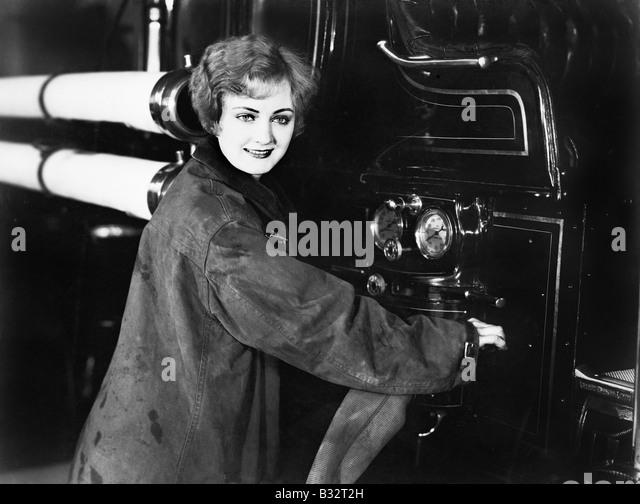 Profile of a young woman standing near a fire truck attaching a hose - Stock Image