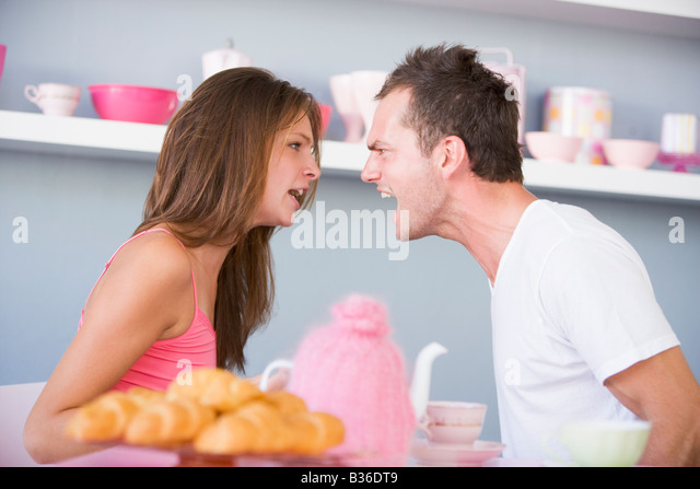 Young couple sitting at a table arguing - Stock Image