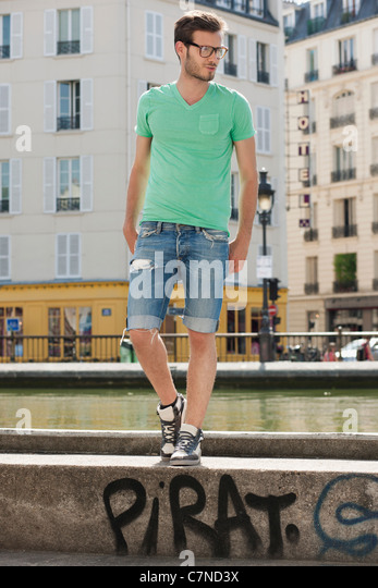 Man standing on the ledge of a canal, Canal St Martin, Paris, Ile-de-France, France - Stock Image