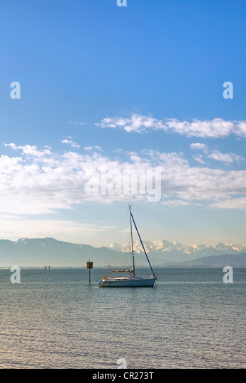 a lone sailing boat in the morning on a calm lake - Stock Image