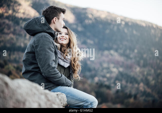 Romantic young couple dating in winter, they are sitting together, she is looking at her boyfriend - Stock-Bilder